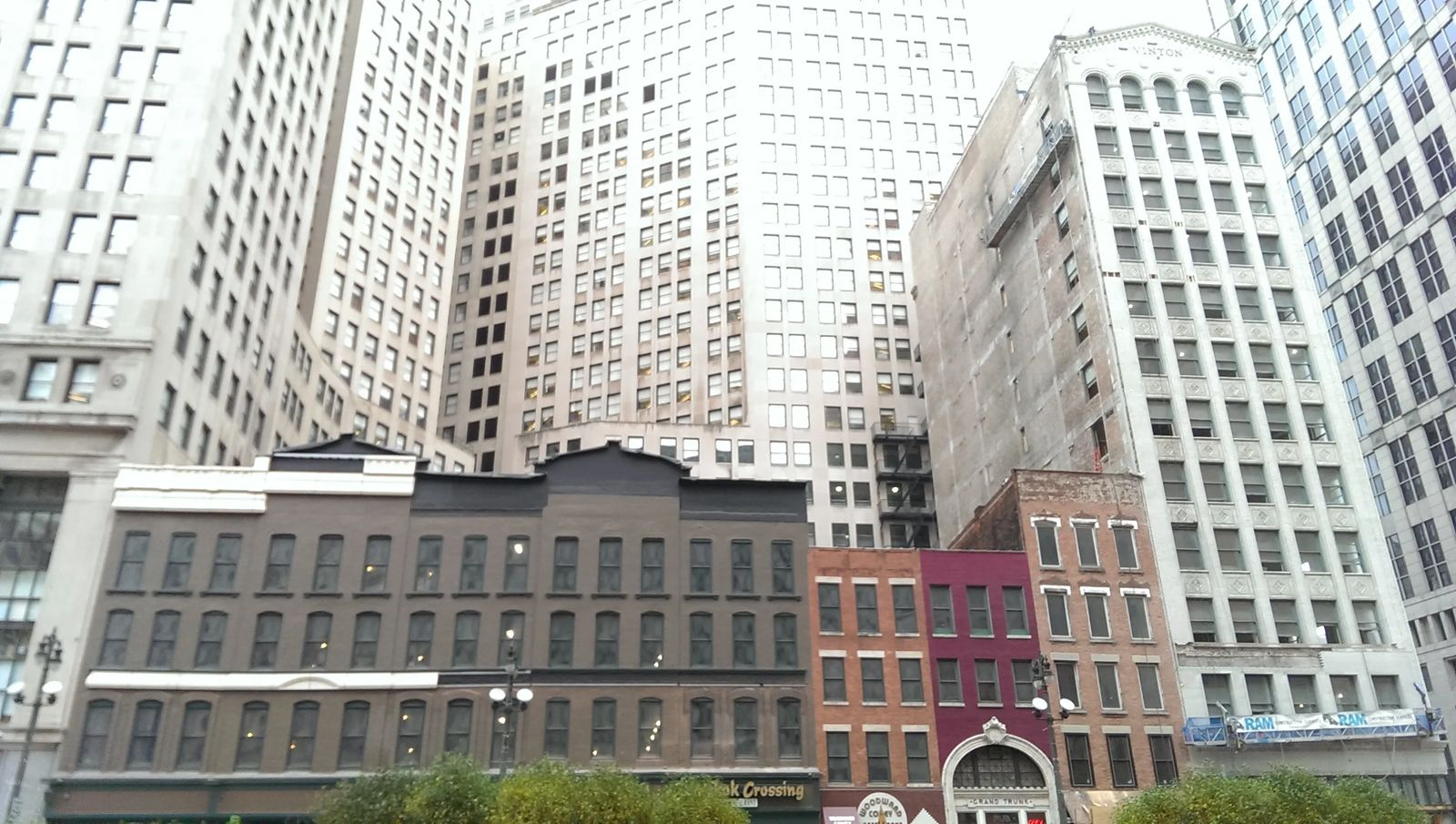 Photo of small buildings dwarfed by nearby skyscrapers in Detroit, Michigan